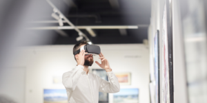 A man wearing virtual reality goggles inside an art gallery