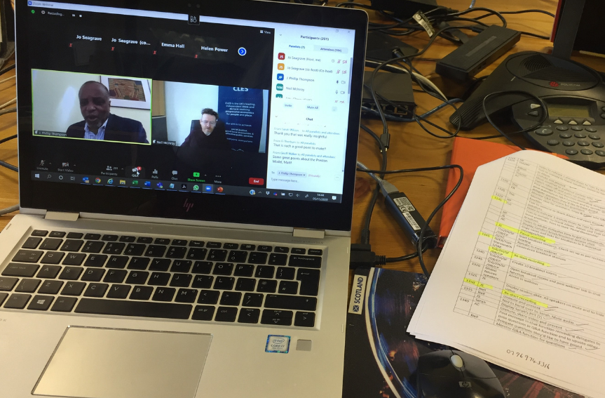 Laptop displaying online event with schedule sitting next to it on a desk